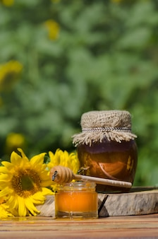 Miód w szklanych słoikach i zachodnia pszczoła miodna. pszczoła miodna. pszczoła siedzi na szklance miodu. chochla i miód w słoiku