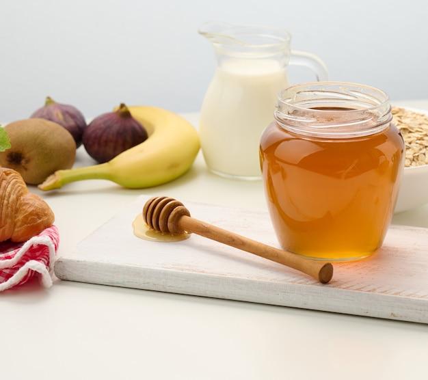 Miód w szklanym przezroczystym słoiku i drewnianym patyczku na białym stole