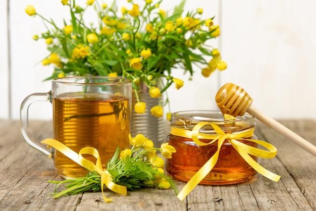 Miód w szklanym słoiku z żółtymi kwiatami.