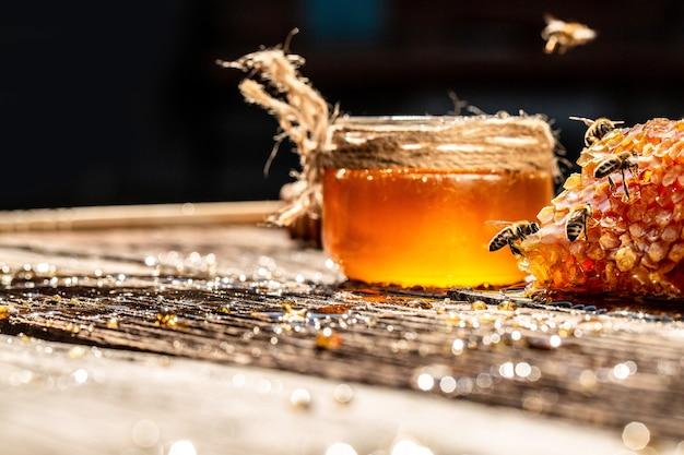 Miód w szklanym słoju z pszczołą latającą na drewnianym stole na tle plastrów miodu z pełnymi komórkami miodu