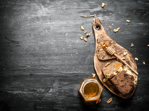 Miód w tle. chleb owocowy z naturalnym miodem i orzechami włoskimi. na czarnym rustykalnym stole.