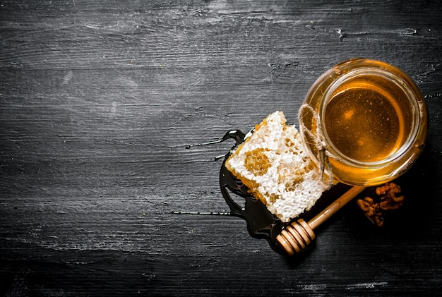 Miód w tle. naturalny plaster miodu i szklany słoik. na czarnym rustykalnym stole.