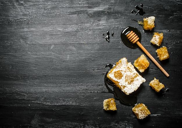 Miód w tle. naturalny plasterek miodu i drewniana łyżka. na czarnym rustykalnym stole.