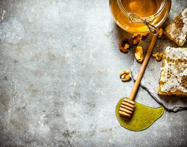 Miód w tle. naturalny słodki miód z łuskanymi orzechami włoskimi. na kamiennym stole.