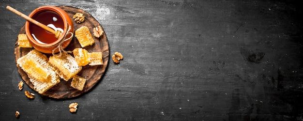 Miód w tle. świeży miód w garnku z orzechami. na czarnej tablicy.