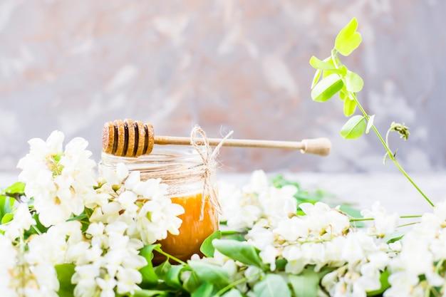 Miód z akacji i innych nektarów wśród gałęzi kwitnących akacji