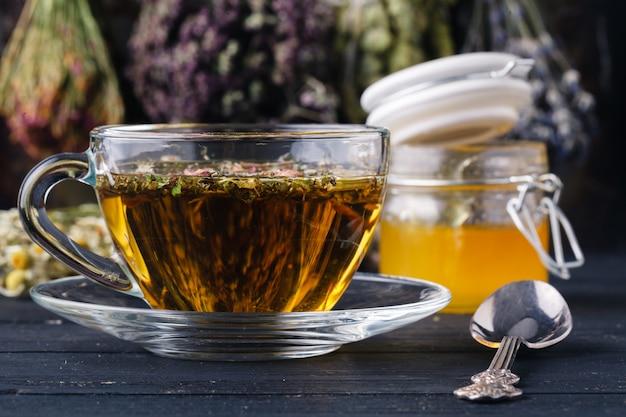 Miód z herbatą na rustykalnym stole backgound z ziołami