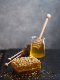 Miód z miodem; drewniana łyżka i pyłek pszczeli