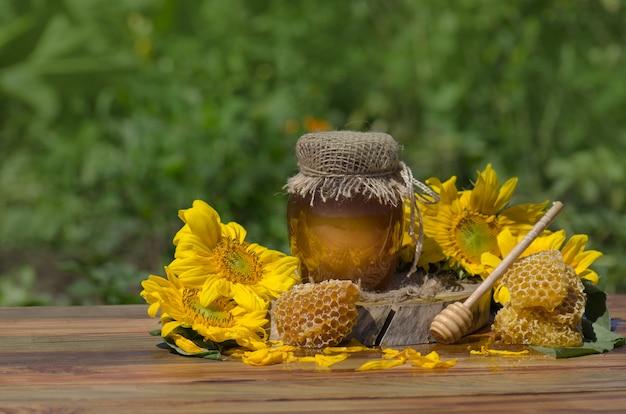 Miód z miodową chochlą na drewnianym stole. organiczny kwiatowy miód przeciwko niewyraźnej naturze z kwiatami. skopiuj miejsce na tekst