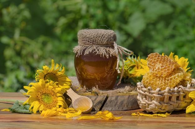 Miód z miodową chochlą na drewnianym stole. organiczny kwiatowy miód