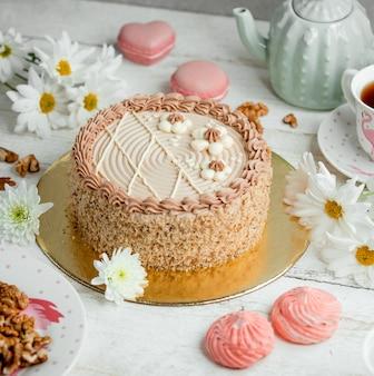 Miodowy tort z różową śmietanką na stole
