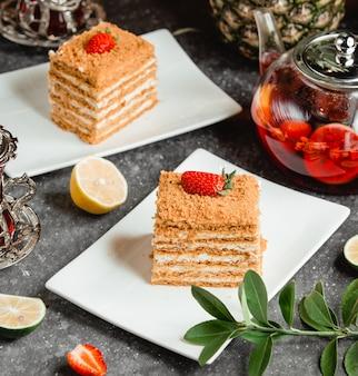 Miodowy tort z truskawkami na nim na białym talerzu