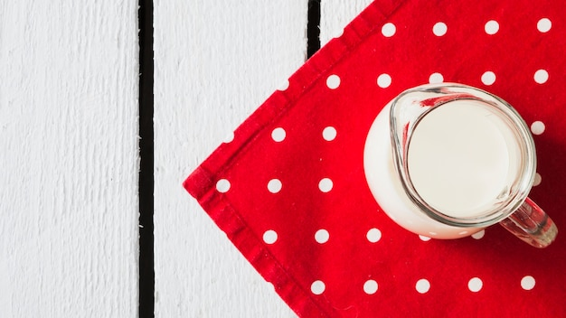 Miotacz mleka na serwetce z czerwoną kropką na białym stole