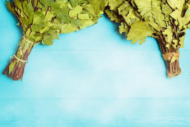 Miotła brzozowo-dębowa do sauny na niebieskiej drewnianej półce. widok z góry.