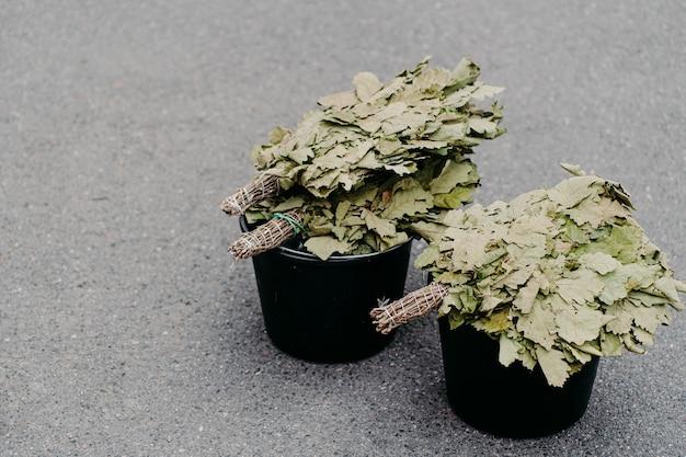 Miotły wykonane z suchych gałęzi dębu na wiadrach