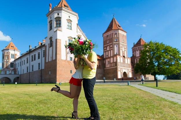 Mir, białoruś. para całuje przed castle complex mir w słoneczny dzień z niebieskim tle nieba. stare średniowieczne wieże i mury tradycyjnego fortu z listy światowego dziedzictwa unesco