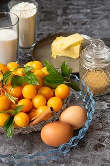 Mirabelka z żółtej śliwki i składniki śliwkowego ciasta. naczynie do pieczenia, jajka, cukier, mąka sezon owoców letnich. zbiór.