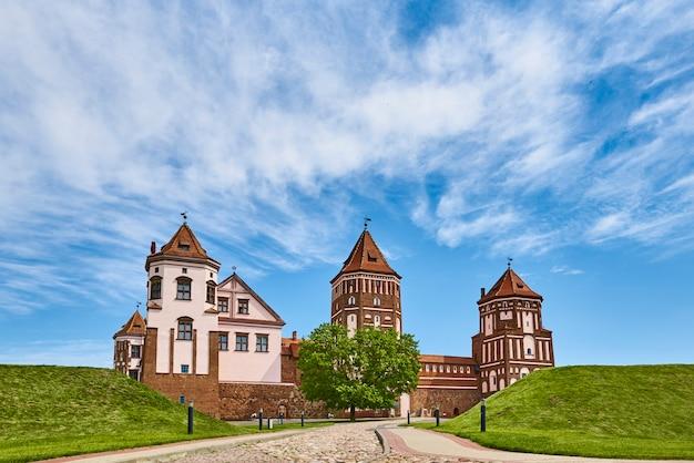 Mirski kompleks zamkowy w letni dzień z błękitnym pochmurnym niebem. turystyczny punkt orientacyjny białorusi, zabytek kultury, stara twierdza