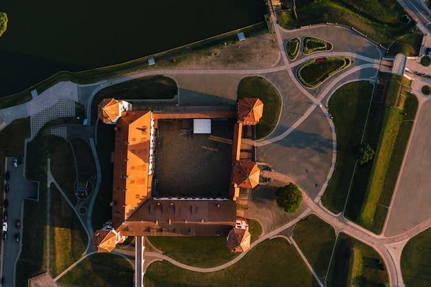 Mirski zamek z iglicami w pobliżu jeziora z widokiem z góry na białorusi w pobliżu miasta mir.