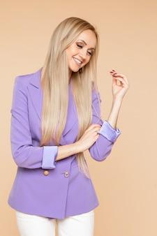 Mirthful piękna długowłosa kobieta w eleganckiej kurtce, odwracając wzrok i uśmiechając się