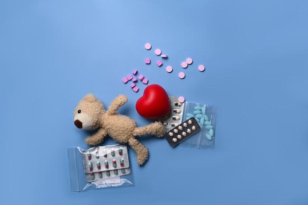 Miś i pigułki medyczne na niebieskim tle.