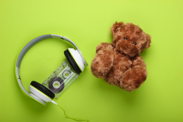 Miś i słuchawki stereo z kasetą audio na zielonej powierzchni