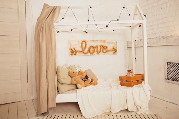 Miś na drewnianym łóżku w białym dziecięcym wnętrzu sypialni.