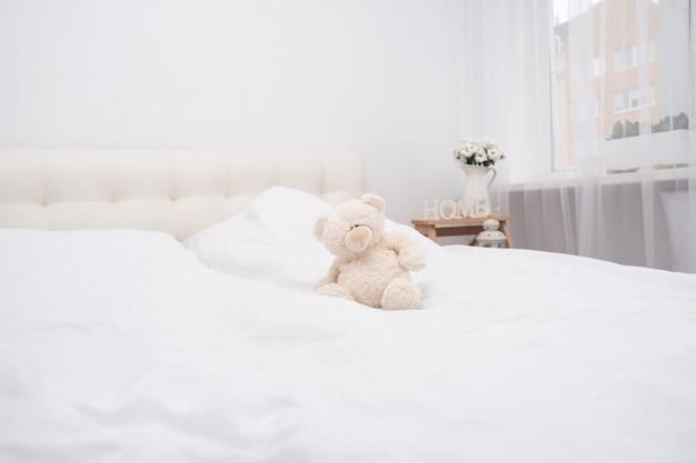 Miś na łóżku na białej pościeli.