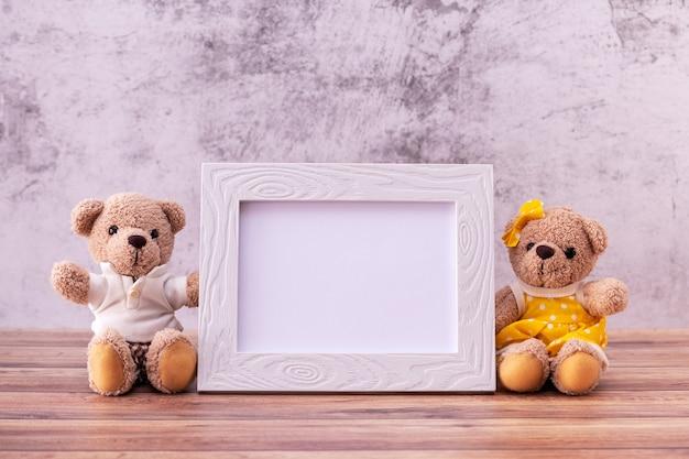 Miś para z ramką na zdjęcia na drewnianym stole.