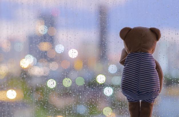 Miś płacze samotnie przy oknie podczas deszczu z kolorowymi światłami bokeh.