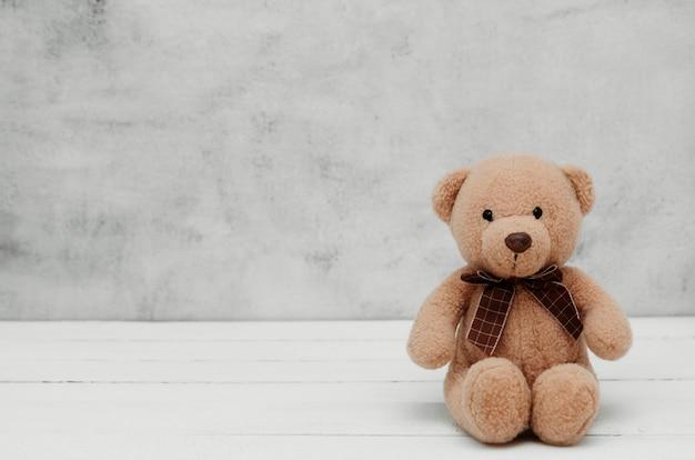 Miś pluszowa zabawka na szarym tle, odizolowywającym. koncepcja edukacji, rodzicielstwa i dzieciństwa. skopiuj miejsce