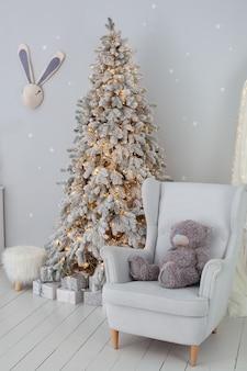Miś siedzi na szarym fotelu w pobliżu choinki z prezentami
