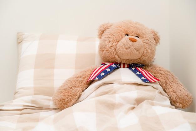 Miś śpi w łóżku.