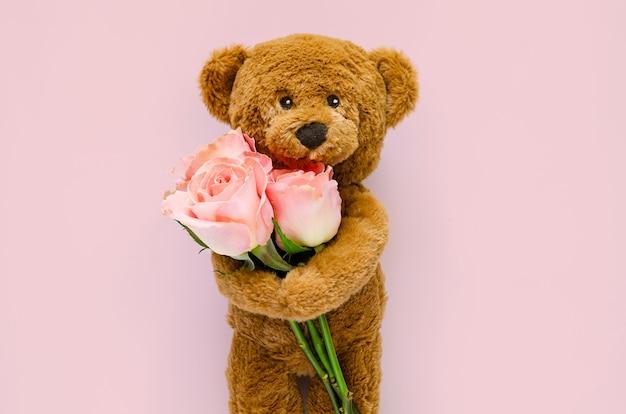 Miś trzyma różowe róże