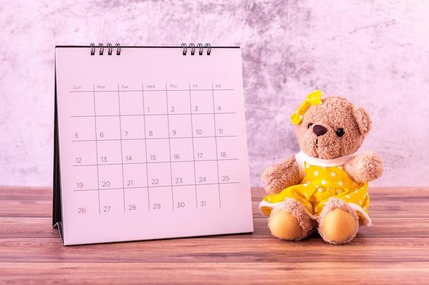 Miś z kalendarzem na drewnianym stole.