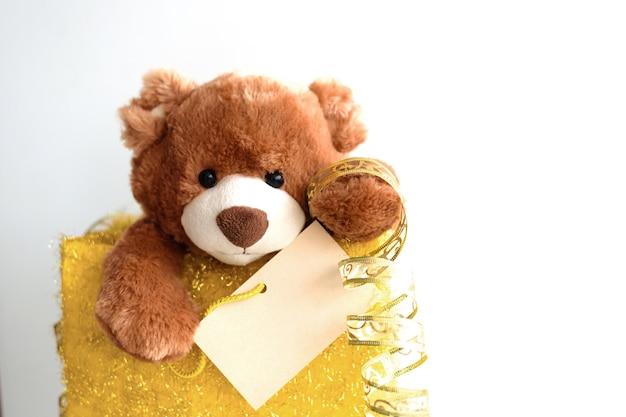 Miś z kartką świąteczną i świąteczną dekoracją i prezentami