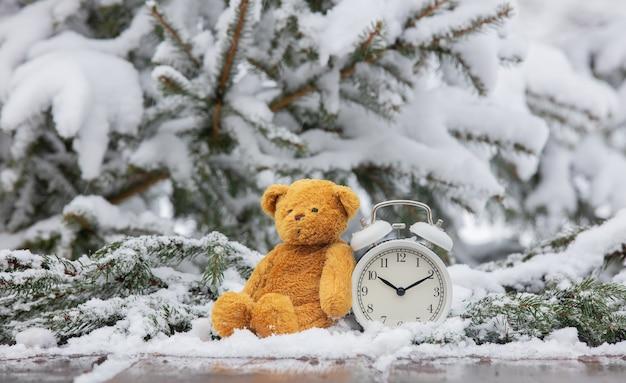 Miś zabawka i budzik na drewnianym stole w śniegu
