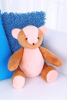 Miś zabawka z poduszkami na kanapie