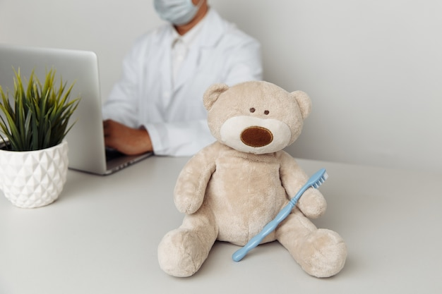 Miś ze szczoteczką do zębów w biurze dentystów koncepcja opieki zdrowotnej dziecka