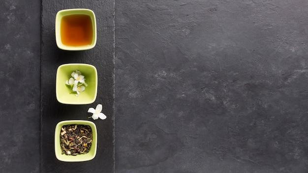 Miseczka herbaty i jej składnik układają się w rzędzie na łupkowym kamieniu nad czarną powierzchnią