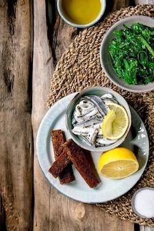 Miseczka marynowanych anchois lub filetów z sardynek w oleju, podana z cytryną, oliwą, solą i opiekanym chlebem żytnim