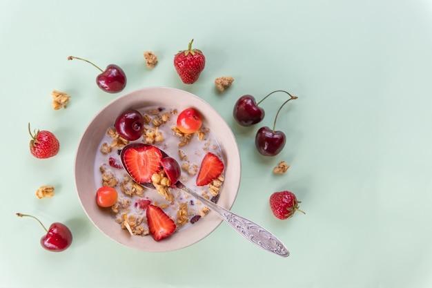 Miseczka musli i jogurtu ze świeżymi wiśniami, truskawkami. śniadanie dietetyczne - miseczki płatków owsianych, jagody