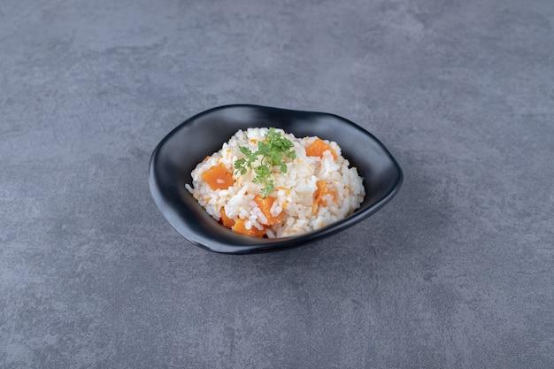 Miseczka ryżu marchewkowego na marmurowej powierzchni.