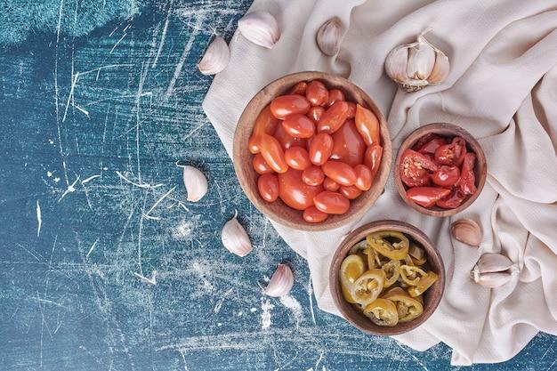 Miseczki marynowanych pomidorów i jalapenos na niebiesko z czosnkiem i obrusem. widok z góry.