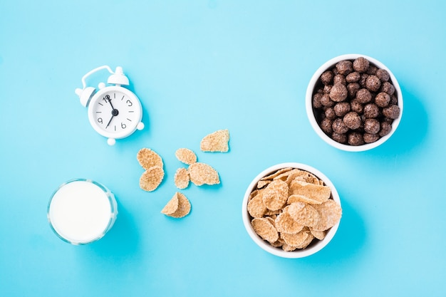Miseczki z płatkami zbożowymi i kulkami czekoladowymi, szklanka mleka i budzik na niebieskim stole. zaplanowane śniadanie, wybór dań. widok z góry