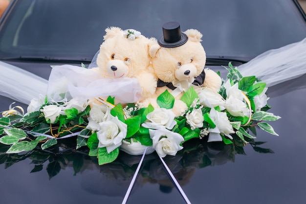 Misie i kwiaty na masce czarnego samochodu. samochód do ślubu. ścieśniać.