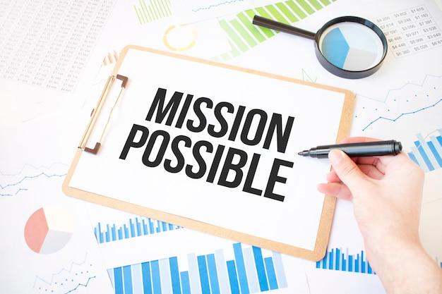 Misja tekstowa możliwa na białej kartce papieru i markerem na dłoni biznesmena na schemacie.