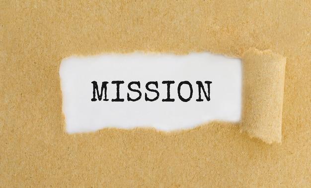 Misja tekstowa pojawiająca się za podartym brązowym papierem.