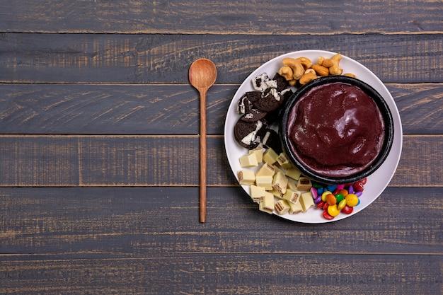 Miska açai z ciasteczkami, kawałkami czekolady, orzechami i czekoladą w polewie na drewnianym stole