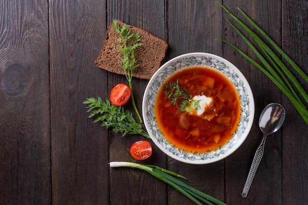 Miska barszcz czerwony buraczany z białą śmietaną na podłoże drewniane, widok z góry. pyszna zupa buraczana. tradycyjna kuchnia ukraińska